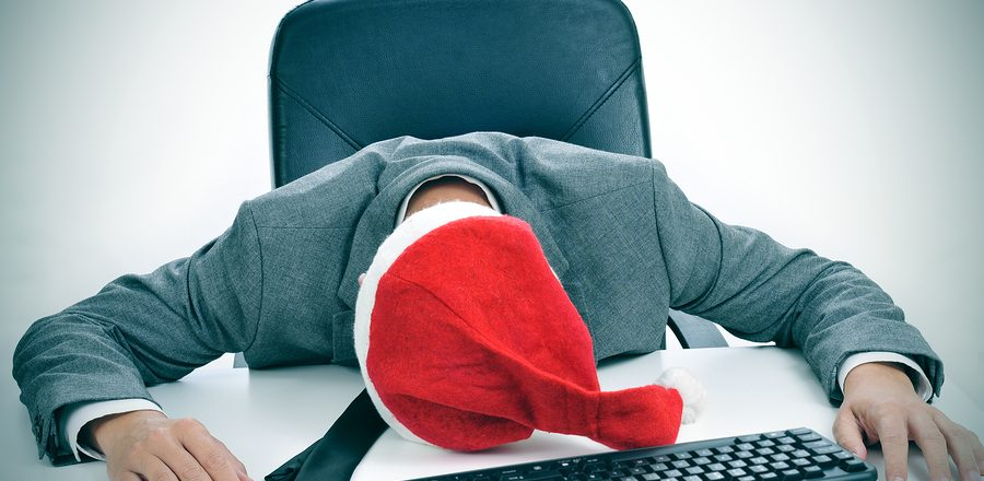 a man in suit with a santa hat sleeping in his desk after an off